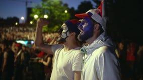Individuo con la cara de la pintura que grita en placer de la victoria del fútbol del partido almacen de video