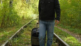 Individuo con la maleta que camina a lo largo del ferrocarril almacen de metraje de vídeo