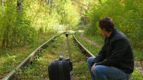 Individuo con la maleta que camina a lo largo del ferrocarril metrajes