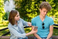 Individuo con la muchacha en la naturaleza Una mujer está señalando en el smartphone El individuo mira correspondencia con el aso Fotografía de archivo libre de regalías