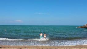 Individuo con la muchacha que corre en el mar almacen de video