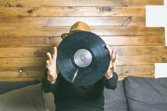 Individuo con los cascos de la música y vinilo en sus manos imagen de archivo