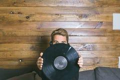 Individuo con los cascos de la música y vinilo en sus manos fotografía de archivo