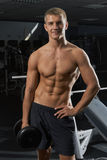 Individuo con pesas de gimnasia en el gimnasio Fotografía de archivo