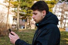 Individuo con un teléfono elegante usando en el parque Fotos de archivo libres de regalías