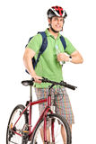 Individuo con una bici de montaña que sostiene una botella de agua Imagen de archivo