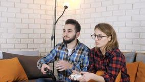 Individuo con una muchacha que se sienta en el sofá y que juega fps de un juego 50 de la consola