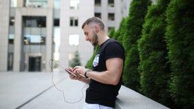 Individuo con una tableta y los auriculares cerca del centro de negocios almacen de metraje de vídeo