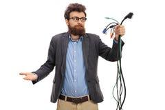 Individuo confuso que mira diversos tipos de cables electrónicos Imágenes de archivo libres de regalías