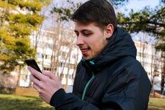 Individuo de la felicidad con un teléfono elegante usando en el parque Imagen de archivo libre de regalías
