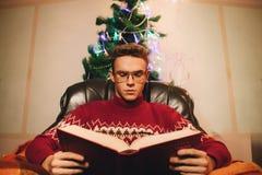 Individuo de la lectura en el fondo del árbol de navidad y de la chimenea Fotos de archivo