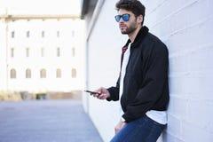 Individuo de moda en vaqueros ligeros, una camiseta blanca y una chaqueta oscura Imágenes de archivo libres de regalías