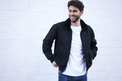 Individuo de moda en vaqueros ligeros, una camiseta blanca y una chaqueta oscura Imagen de archivo libre de regalías