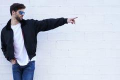 Individuo de moda en vaqueros ligeros, una camiseta blanca y una chaqueta oscura Fotos de archivo libres de regalías