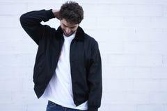 Individuo de moda en vaqueros ligeros, una camiseta blanca y una chaqueta oscura Foto de archivo libre de regalías