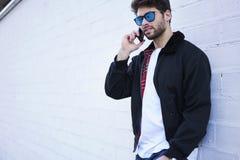 Individuo de moda en vaqueros ligeros, una camiseta blanca y una chaqueta oscura Fotografía de archivo libre de regalías