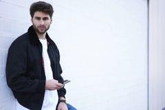 Individuo de moda en vaqueros ligeros, una camiseta blanca y una chaqueta oscura Fotos de archivo