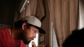 Individuo de ojos azules del inconformista con una barba y un snapback del casquillo que come una hamburguesa del bocadillo en un almacen de video