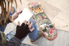 Individuo de Rasta que sienta al aire libre el trabajo en un applie caliente de los tonos de la tableta Foto de archivo