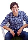 Individuo de risa en silla sobre blanco Foto de archivo libre de regalías