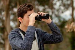 Individuo del adolescente que mira con los prismáticos Fotografía de archivo