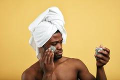 Individuo del Afro que usa la crema después de tomar una ducha aislada sobre fondo amarillo imagen de archivo libre de regalías