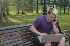 Individuo del inconformista que llama vía el teléfono móvil y que lee la información del netbook foto de archivo libre de regalías