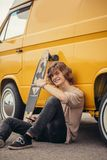Individuo del inconformista que sienta después su coche amarillo durante viaje por carretera fotografía de archivo