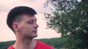 Individuo del primer, fondo rojo del árbol verde, mirada de la camiseta lejos, en cámara, sonrisa metrajes