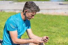 Individuo deportivo que escucha la música mientras que entrena Fotografía de archivo