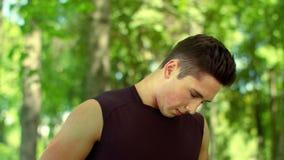 Individuo deportivo que hace estirando el ejercicio para el cuello Entrenamiento del hombre joven al aire libre almacen de metraje de vídeo