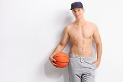 Individuo descamisado joven que lleva a cabo un baloncesto Imágenes de archivo libres de regalías