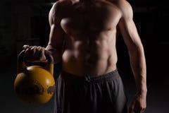Individuo descamisado que lleva a cabo una pesa de gimnasia Imagenes de archivo