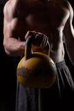 Individuo descamisado que lleva a cabo una pesa de gimnasia foto de archivo libre de regalías