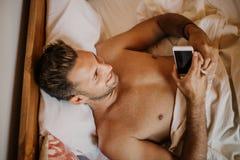 Individuo despreocupado que disfruta de nuevo día Hombre joven hermoso en cama que mecanografía en el teléfono celular, enviando  foto de archivo