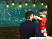 Individuo devuelto y pequeño niño en la sala de clase Muchacho lindo que juega con el bigote del hombre Niño sonriente en la grad foto de archivo