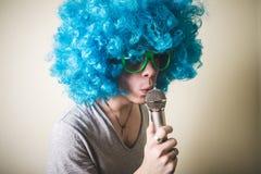 Individuo divertido con la peluca azul que canta Foto de archivo libre de regalías