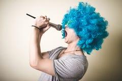 Individuo divertido con la peluca azul que canta Imagen de archivo