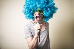 Individuo divertido con la peluca azul que canta Foto de archivo