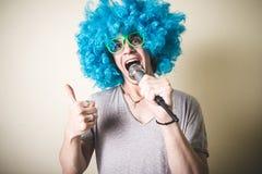 Individuo divertido con la peluca azul que canta Fotos de archivo