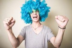 Individuo divertido con la peluca azul que canta Fotografía de archivo libre de regalías