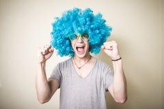 Individuo divertido con la peluca azul que canta Imagenes de archivo