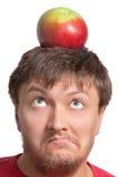 Individuo divertido con una manzana en su cabeza Fotografía de archivo libre de regalías