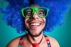 Individuo divertido descubierto con la peluca azul y el lazo rojo Foto de archivo