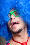 Individuo divertido descubierto con la peluca azul y el lazo rojo Foto de archivo libre de regalías