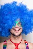 Individuo divertido descubierto con la peluca azul y el lazo rojo Imagen de archivo