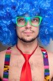 Individuo divertido descubierto con la peluca azul y el lazo rojo Imagen de archivo libre de regalías