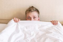 Individuo divertido en cama debajo de la manta despu?s de dormir Hombre so?oliento que despierta fotografía de archivo libre de regalías