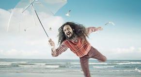 Individuo divertido que sostiene un paraguas en una playa Imagen de archivo libre de regalías