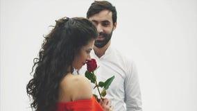 Individuo elegante hermoso en una camisa clásica con las rosas rojas en sus manos Aparece en un fondo blanco Da las rosas a